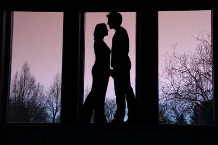 Silhouette of couple standing face to face Stockfoto