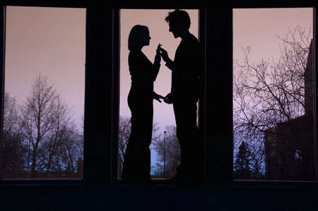Silhouette of couple facing each other and touching hands
