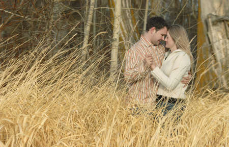 Couple holding each other in a field of wheat Stockfoto