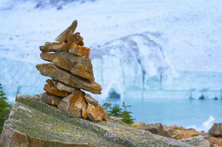 Cairn in front of glacier, ice cave and mountain
