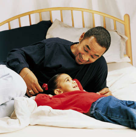 nurturing: Father and little girl talking on a bed
