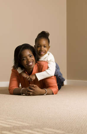 Woman and girl cuddling on the floor Stock Photo - 7559281