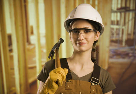 tradeswoman: A woman wearing construction hat and holding a hammer