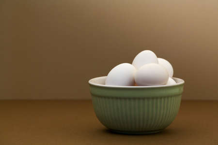 close up food: White eggs in green bowl on brown table