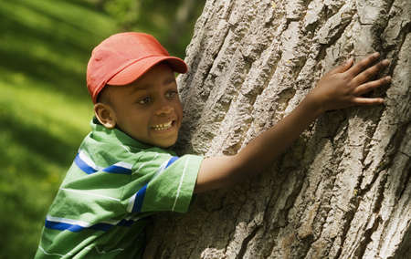 Boy hugging tree trunk