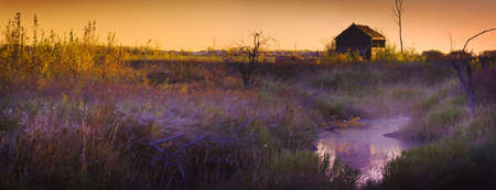 farm structure: Abandoned shack at sunset near a creek