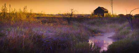 gramineas: Choza abandonada al atardecer cerca de un arroyo