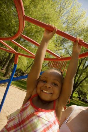Young girl swinging on playground equipment Stock Photo - 7559337