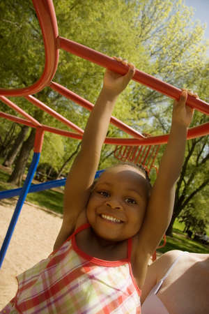 play time: Young girl swinging on playground equipment