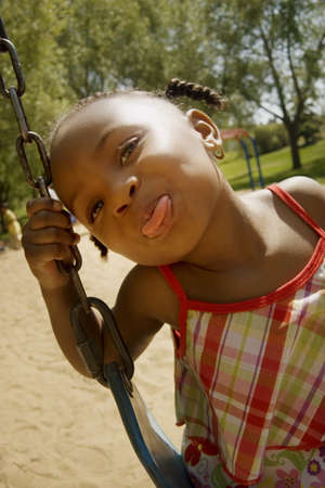 silliness: Young girl sticking out her tongue while on the swing set at the park