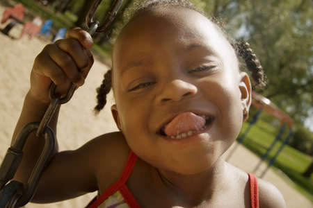 silliness: Young girl sticking out her tongue while on the swingset in the park LANG_EVOIMAGES