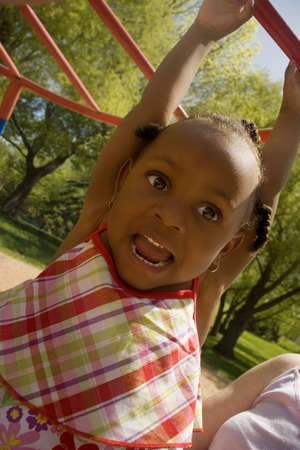 Young girl hanging from playground equipment Stock Photo