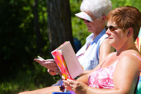 60 years old: Two woman reading and sunbathing