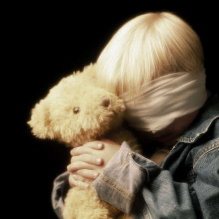 miserable: Boy with bandage on eyes and holding teddy bear LANG_EVOIMAGES