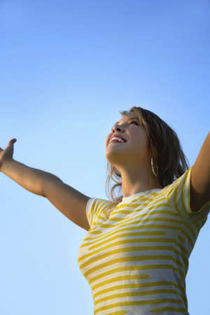 worshipping: Female looking upwards with arms outstretched