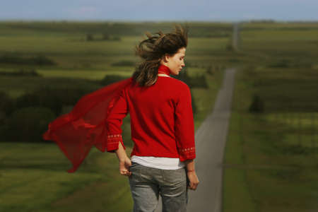 Woman walking on road surrounded by fields Stock Photo - 7559373