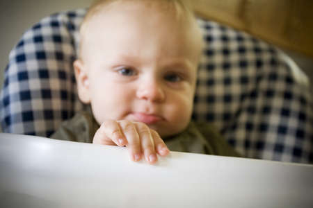 Baby boy pouting in highchair Stock Photo - 7559375