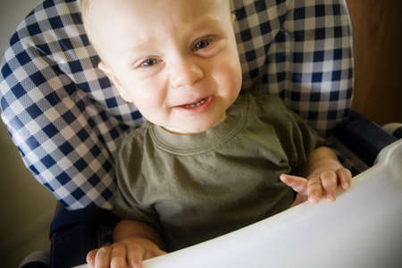 Baby boy crying in highchair Stock Photo - 7559398