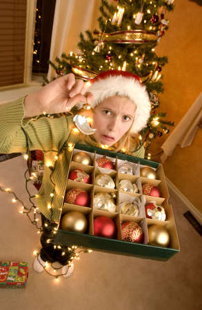 Teenage girl tangled in christmas lights holding decorations Stock Photo - 7559334