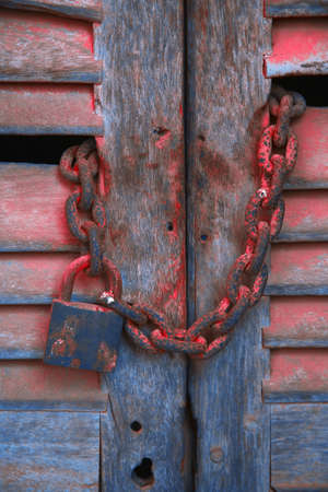 Padlock and chain on wooden door