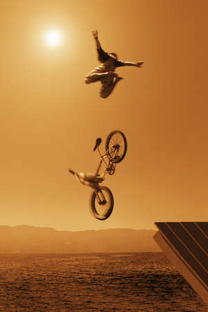 Cyclist going off jump into water in brown tones Stock Photo