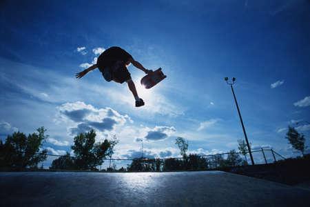 skateboarding tricks: Skateboarder jumping in skate park