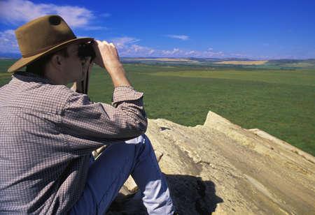 cliff edge: Hiker with binoculars on cliff edge