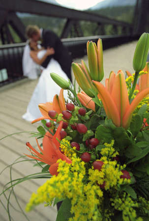 Bouquet of flowers with bride and groom kissing in the background Reklamní fotografie