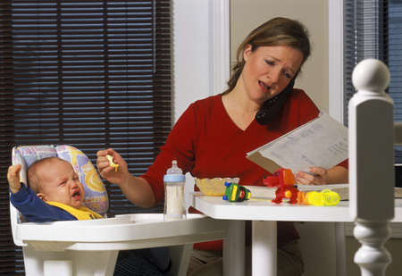 highchair: Woman talking on portable phone, reading notes, and feeding baby in highchair