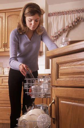Girl putting dishes into dishwasher photo
