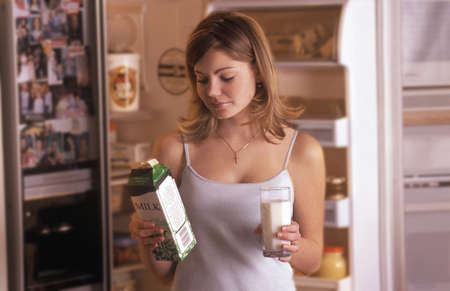 fridge: Girl getting glass of milk from fridge