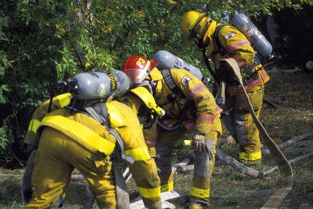 corey hochachka: Firemen outside picking up firehose Stock Photo