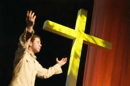 Man worshipping beside cross photo