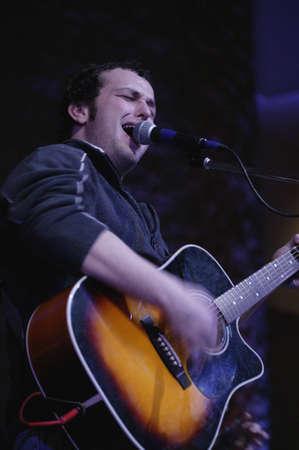 Man singing and playing guitar Stock Photo