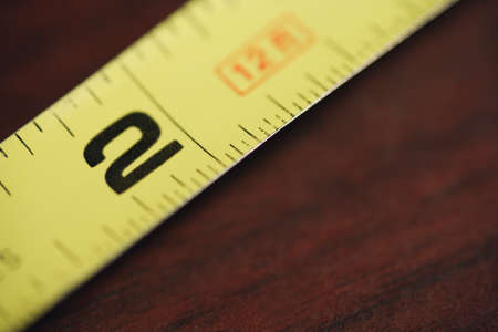 millimetres: Yellow and black tape measure Stock Photo