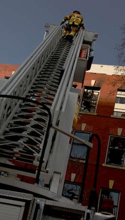 tanasiuk: Fireman on ladder near building Stock Photo