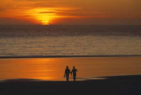 Silhouetted lovers, beach sunset. Imagens