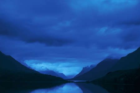 peacefulness: Mountains with dark cloud cover over a lake Stock Photo