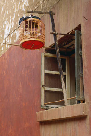 domestication: Birdcage hanging from a window in Beijing, China Stock Photo