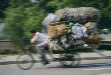 30 something: Man hauling a load of bags on a cycle rickshaw in Beijing, China