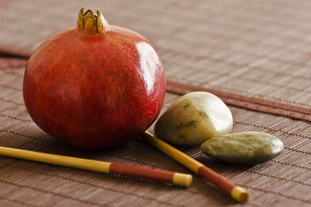 Pomegranate with chopsticks and pebbles photo