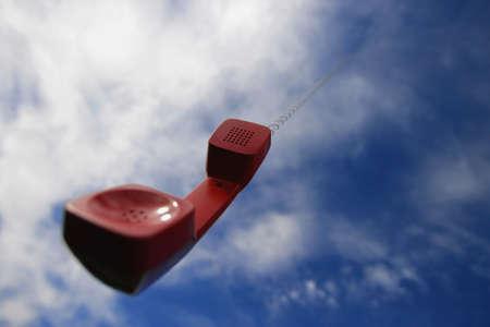 Een telefoon hoorn bungelend uit de hemel