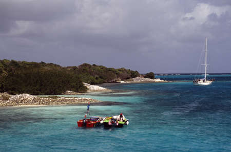 Boats off the shore in the West Indies photo