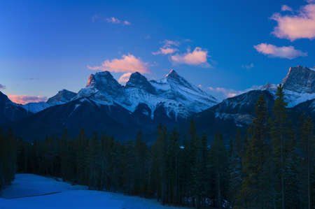 the mountain range: Three Sisters Mountain Range at sunrise, Canmore, Alberta, Canada Stock Photo