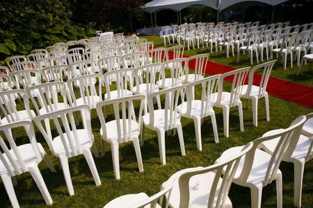 Rows of white chairs outdoors
