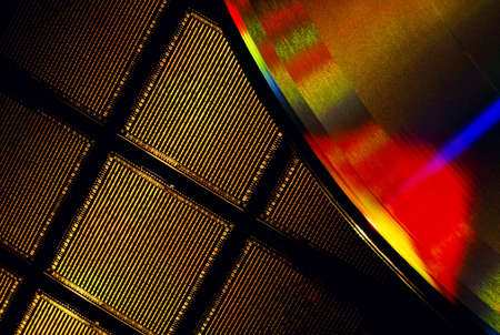 Close-up of a microchip wafer and a compact disk