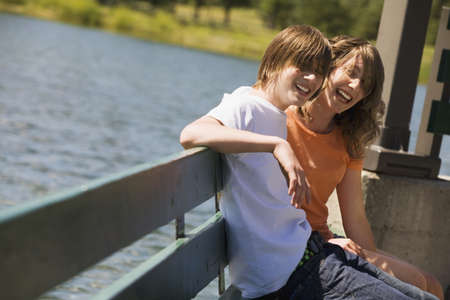 Teenagers sitting on a bench by water Stock Photo - 8245435