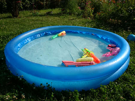 Childrens swimming pool with toys in summer garden