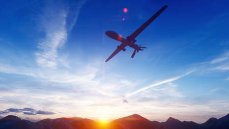 A military drone flies over a desert mountain plain at sunset. Stock Photo