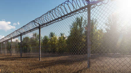 The suns rays and autumn trees are visible through the metal prison fence with barbed wire. 3D Rendering